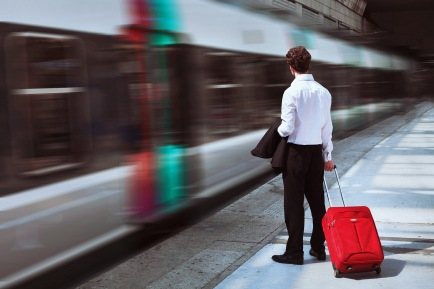 man-with-suitcase-on-railway-platform watching commuter train