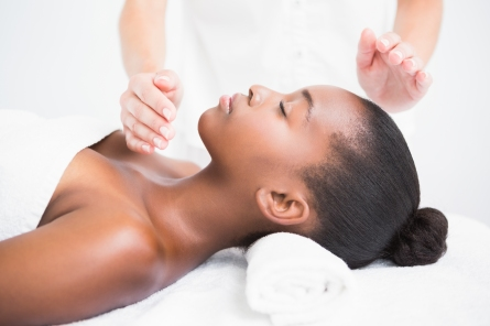 Woman on massage couch with white towels receiving Reiki